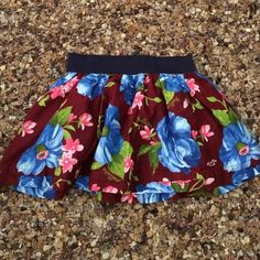 Hollister Skirt This super cute blue, burgundy and green flower skirt has the sea gull Hollister insignia on the front of the skirt. It has an elastic waistband with a liner inside the skirt. Hollister Skirts