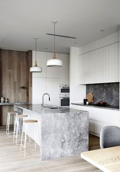 This kitchen from Mim Design pairs black and grey marble with white cabinets and wood accents, for a look that's minimal but also gives you plenty to look at.