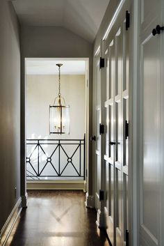 Beautiful railing for a balcony or and open space.  Indoor/outdoor hanging light fixture, white cabinets and dark floors.