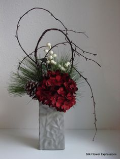 This modern holiday arrangement features shaped branches with a deep red hydrangeas and iced white berries. All in a soft gray colored 8 h x 4 w x 2 d ceramic vase. Overall size 21 h x 13 w x 6 d