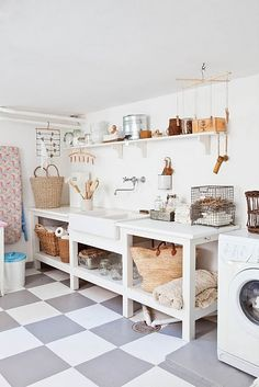Budget laundry room - Checker painted concrete subfloor, and simple, easy to build workstation. Reuse our old sink, reuse old cabinets from kitchen, Washer/Dryer elevated on concrete slabs.