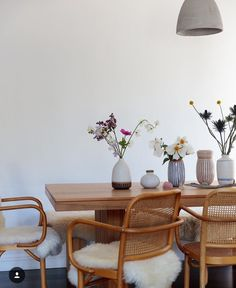 wooden dining table, sheep skin, vases, grey pendent light