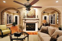Interior Living Room Brick Double Open Doorway Design Luxury Ceiling Fan Painting On The Wall Modern Fireplace Design Hexagon Living Table Design With Glass On The Top White Carpet Wood Flooring Home Décor to Impress Your Guests