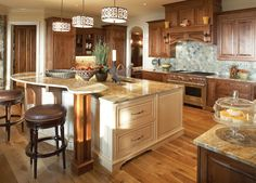 White kitchen island in natural wood kitchen design. Island includes adjacent elevated counter creating a 2-tier island resulting in a dedicated counter dining space as well as dedicated work space