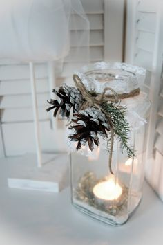 Table decor - nstant coffee glass, embellished with lace, white painted pine cones, and some hemp string.