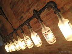 This industrial style lamp is constructed from heavy-duty black iron piping. The 9 customizable bottles are firmly secured by a custom rubber gasket that secures the bottle without causing damage. A low wattage bulb is used to illuminate the vintage  bottle producing a warm ambient glow. Each bottle is etched on the inside in order to diffuse the light and can easily be removed by hand for quick bulb replacement.  http://www.pearedcreation.com/shop/spirit-of-kentucky/
