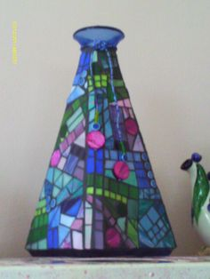 Mosaic Bottle- stained glass, mother of pearl disc beads and charcoal gray grout make up this gorgeous bottle by Debbi Haas