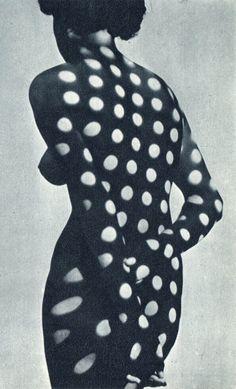 Photo en noir et blanc de Heinrich Heidersberger montrant un nu féminin sur lequel des pois de lumière sont projetés #surrealism #polkadots #photo #art #blackandwhite