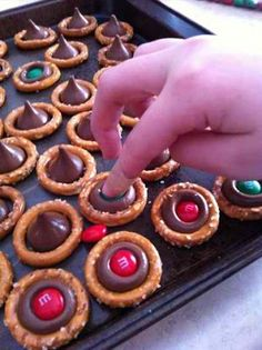 Reindeer noses. Preheat your oven to 225 degrees. spread the round pretzels on a cookie sheet so that they lie flat. Place one kiss in each pretzel.Allow the kisses to melt. Don't leave the room. This really takes only 3 or 4 minutes. press one M into each kiss. Push them around a little so that chocolate touches all of the edges of the pretzels.