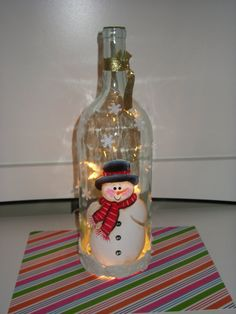 I painted this cute little snowman on the wine bottle, drilled a hole in the bottom of the bottle and inserted a 10 light strand of lights. The bottom of the bottle has textured snow and I have put some snowflake cutouts on the bottle. Just looks sooooo frosty.