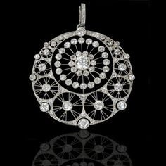 Beautiful Edwardian pierced platinum pendant designed as a circular openwork plaque comprising of floral diamond set motifs and delicate millegrain settings with removable brooch fitting, English, circa 1910