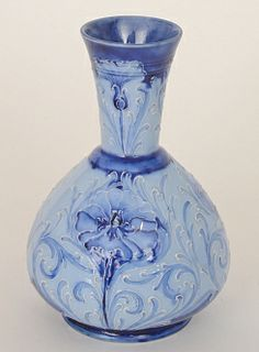William Moorcroft - James Macintyre & Co - Florian - A vase of shouldered ovoid form with a flared collar neck decorated with stylised flowers and foliate scrolls in tonal blue over a pale blue washed ground, Florian printed mark and green flash painted monogram, height 13.5cm