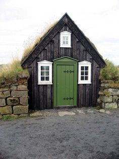 tiny black house with green door in reykjavik, iceland