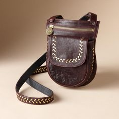 """When just the essentials will do. Calleen Cordero's scaled-down bag in leather gets its edgy detailing from solid brass dashes studded along its pouch and 48""""-long sling strap. Zippered main compartment"""