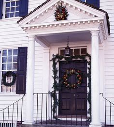 Colonial Welcome - Wreaths decorated with fruit adorn the front door and pediment of this home, dressing up the entrance and calling attention to the pediment's dentil molding. The wreaths are made of magnolia leaves and include pineapples, a Colonial-era symbol for lavish hospitality.