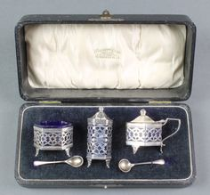 Lot 466, A silver 3 piece hexagonal condiment set with pierced decoration and blue glass liners, together with a spoon Birmingham 1918, 64 grams, est £70-100