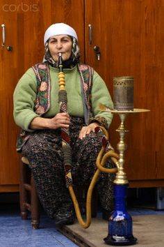 Woman smoking water-pipe in Istanbul. There is water in base of pipe. Called a Hookhah cools down the smoke.