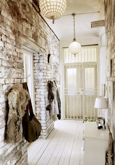 that is one sexy entry.... white brick, 2 stunning ball chandeliers, white wood floors, fur & leather casually hanging on hooks.....