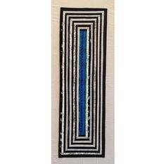 Quilted geometric table runner in black and white with a blue river running down the center. By AnnBrauer. Quilt as you go. About 11 x 40 inches. Cotton, cotton batting. Simple and minimal.
