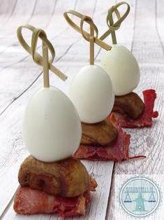 Verjaardagshapje met gekookt kwartelei, een halve gebakken champignon en een stukje gebakken bacon. Hoe je dit hapje en nog 5 andere ei-hapjes maakt vind je bij de bron.