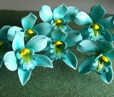 Gum paste flowers..... Cymbidium Orchids...great cake toppers. Made out of gum paste and edible food dye..the color of these are teal with a yellow center and the throat/lip of the orchid is hand painted as well. If you are making your own wedding cake or having someone do it for you, these would great on your cake