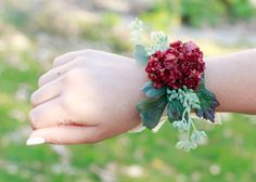 Elegant and chic small corsage to fit any popular romantic burgundy colored theme. This corsage features: - Burgundy Mini Flower Bush - Green Framing - Sage Seeded Eucalyptus Felt and or ribbon backin