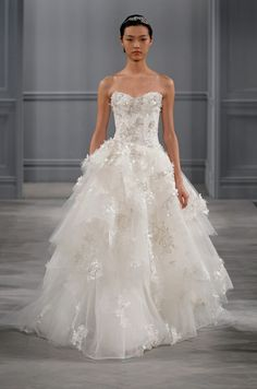 This strapless tiered confection from Monique Lhuillier features a stunning skirt of lace and tulle, complemented by an intricate lace bodice.