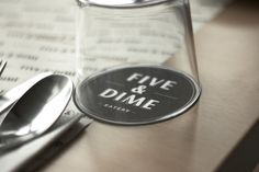 Five & Dime by Bravo Company for a restaurant/café in Singapore. A coin is used as a visual representation of the name. Five & Dime refers to a variety store where everything is sold for 5 or 10 cents. I loive the color palette, the logo, typeface selections... everything is so well designed and makes me want to be there! - glass
