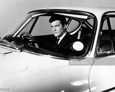 Roger Moore as Simon Templar, in a promotional portrait at the wheel of a Volvo P1800 sports car, for the British spy thriller TV series 'The Saint', 1965.