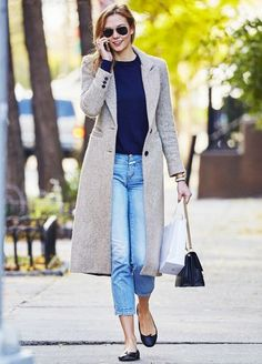 Karlie Kloss wears a navy sweater, long coat, cropped jeans, flats, aviator sunglasses, and a chain strap bag