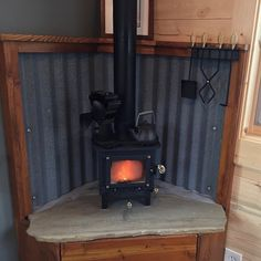 Tool kit hung on the wall with an eco fan on the stove and a small kettle. Wood Stove Wall, Wood Stove Surround, Mini Wood Stove, Wood Stove Hearth, Stove Fireplace, Fireplace Design, Indoor Wood Stove, Garage To Living Space, My Living Room
