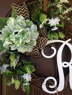 Gorgeous wreath made on 18 grapevine , features 1 large hydrangea blossom in original and beautiful sea foam green color , surrounded by lively greenery including hydrangea leaves , accented with wildflowers and miniature white daffodils . All finished with burlap bow in natural with black chevron design . Add monogram of your choice for a personal touch Thank you for supporting handmade