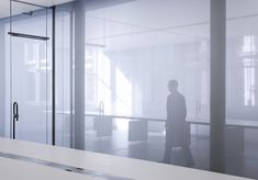 Figures appear as ghostly silhouettes behind the translucent white fabric that partitions these New York offices.