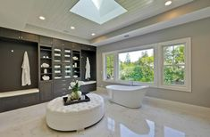Contemporary master bathroom with freestanding acrylic tub, skylight and tufted ottoman