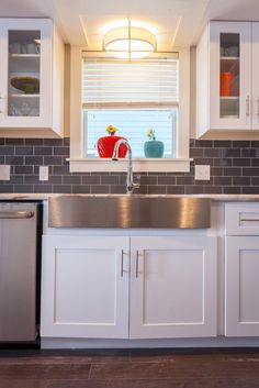 A stainless steel farmhouse sink complements the warm gray subway tile backsplash.