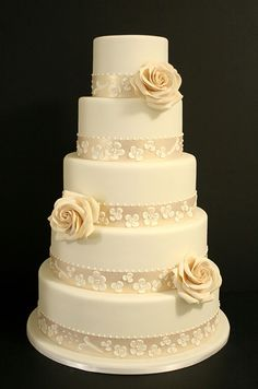 An ivory fondant cake is adorned with champagne ribbon, sugar roses and classic piped pearl and flower details.