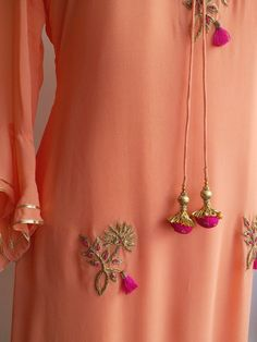 Get noticed in this Peach Georgette Tunic with delicate Zardozi bootas All-over. It is detailed with a Tasseled Tie-up on the Neckline and embroidery motifs are accentuated with delicate resham tassels. The sleeves are three quarter with gota frill detail Pakistani Dresses, Indian Dresses, Indian Outfits, Anarkali Dress, Kurta Designs, Blouse Designs, Ethnic Fashion, Indian Fashion, Embroidery Suits Punjabi