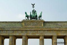 No es un Arco del triunfo, es solamente una de las 18 antiguas puertas de Berlín hacia finales del 1700.  La puerta está coronada con una escultura de cobre de unos 5 m de altura, la cuadriga, que representa a la Diosa Victoria, montada en un carro tirado por cuatro caballos en dirección a la ciudad.   La cuadriga original fue robada por los Franceses, recuperada por los Alemanes, destruida por los aliados, reconstruida, olvidada durante los años del muro y finalmente restaurada en 1991…