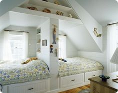 Twin beds, built-in storage, slanted ceiling.
