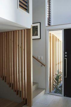 escalier moderne, escalier design en bois clair, avec des motifs rayures en bois comme garde corps, sol en dalles en couleur ivoire, marches en couleur ivoire, tableau avec cadre noir, poignée d'escalier minimaliste en bois clair
