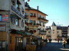Megève: Strada pedonale del paese (stazione di sport invernali ed estivi), con negozi, caffetteria con terrazza e case con finestre e balconi decorati con fiori - France-Voyage.com