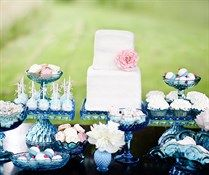 This summer dessert table showcases beautiful white and pink desserts arranged on blue crystal cake pedestals.