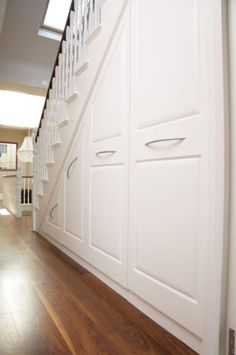 Traditional styling for under stairs storage unit. Elegant curved handles on rai… Traditional styling for under stairs storage unit. Elegant curved handles on rai… Staircase Storage, Basement Storage, Basement Stairs, Stair Storage, House Stairs, Staircase Design, Basement Remodeling, Kitchen Storage, Storage Spaces
