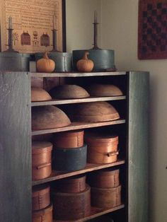 old blue/green cupboard in living room. old blue/green pantry boxes on top.