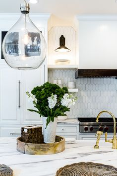 A white kitchen hood with wood trim, flanked by stacked white floating shelves, stands over a white geometric tiled backsplash, Tabarka Terracotta Picket Tiles, and an integrated Wolf cooktop fitted with pot and pan drawers lit by black sconces. Classic Kitchen, New Kitchen, Kitchen Island, Gold Kitchen, Country Kitchen, Beautiful Kitchens, Cool Kitchens, Midcentury Modern, Kitchen Interior