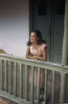 1940's A smiling woman poses on a courtyard balcony of an old former mansion.Trinidad, Cuba//MELVILLE B. GROSVENOR/National Geographic Creative