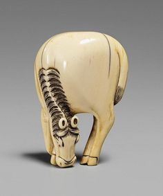 An ivory netsuke of a large grazing horse. Around 1800