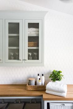 Gray metal lattice cabinets are mounted below a shiplap ceiling on square beveled backsplash tiles above a wood countertop accenting shelves painted in Sherwin Williams Silver Strand.
