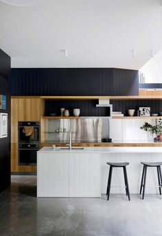 This stunning kitchen space features wall panel cladding painted black paired with timber custom joinery and a stainless steel splashback. The kitchen island features a marble benchtop and timber cladding in white paired with black bar stools. Polished concrete flooring runs throughout the home.