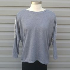 """Gray with Silver Sequined Hi-Lo Top Gray Sequined Batwing Hi-Lo Top. Stretchy with a sequined strip running down the arms. 3/4 length sleeves. Approximate measurements: Bust-52"""" Front Length-27"""" Back Length-32""""  This is NWOT Retail. Price Firm Unless Bundled. Tops Tunics"""